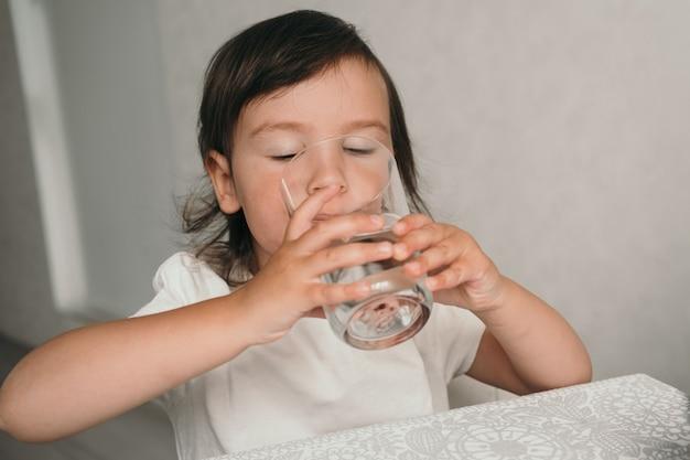 La fille boit de l'eau dans un verre en verre.