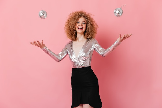 Fille de bonne humeur jongle avec des mini boules disco. portrait de femme bouclée en chemisier brillant sur espace rose.