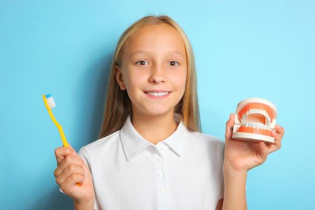Une fille de bonne humeur se brosse les dents et tient un modèle de dents