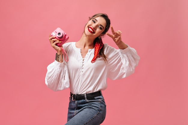 Fille de bonne humeur tient la caméra et montre le signe de la paix sur fond rose. belle dame avec rouge à lèvres en chemisier blanc et jeans sourit.