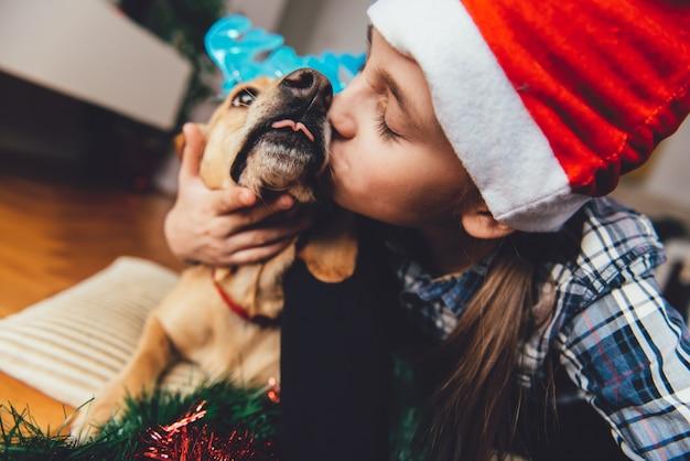 Fille avec bonnet de noel embrassant chien