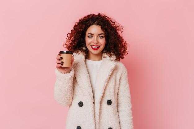 Fille bouclée aux yeux bleus avec rouge à lèvres vêtue d'un manteau de fourrure blanc écologique souriant et tenant un verre de café sur l'espace rose.