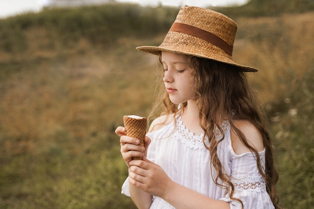 Fille bouclée dans un chapeau de paille mange de la glace dans le village en été
