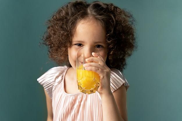 Fille bouclée avec du jus d'oranges