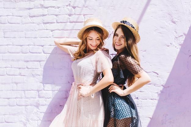 Fille bouclée heureuse en robe vintage légère regardant vers le bas tout en posant à côté de l'adorable sœur