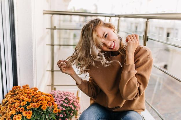 Fille bouclée jouant avec ses cheveux et souriant. jolie jeune femme se détendre au balcon.