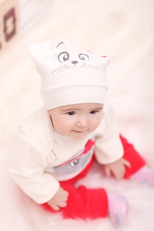 Fille bouclée mignonne enfant en bas âge, debout à une table de dîner de noël régler les plats en préparation pour célébrer noël