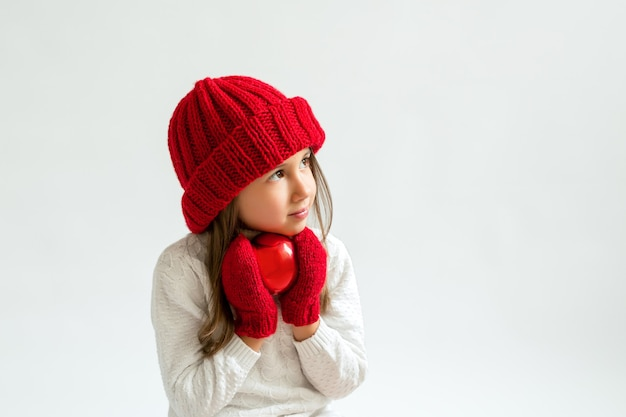 Une fille avec une boule de noël dans un bonnet et des mitaines rouges regarde de côté l'espace de copie