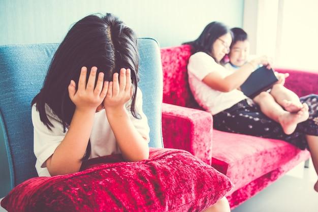 Fille bouleversée assise sur une chaise mère profitant avec son frère du canapé à la maison