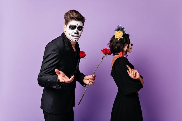 Fille bouleversée en costume de carnaval debout en studio avec son petit ami. homme en costume de mascarade demandant pardon avec rose.