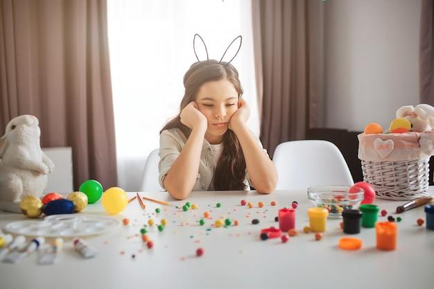 Fille bouleversée se prépare pour pâques. elle est assise à table pleine de bonbons et de décoration colorée. fille seule dans la chambre. triste et bouleversé.