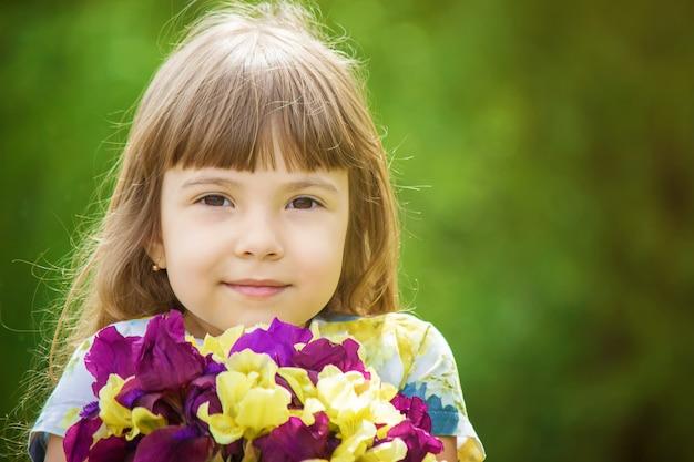 Fille avec un bouquet d'iris. mise au point sélective.