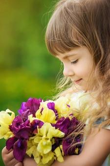 Fille Avec Un Bouquet D'iris. Mise Au Point Sélective. Photo Premium