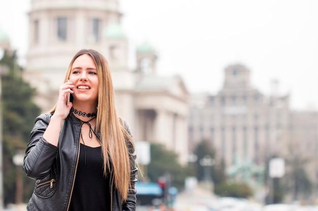 Une fille branchée parle au téléphone tout en se promenant dans le jardin de la ville à l'heure du coucher du soleil.