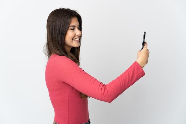 Fille brésilienne d'adolescent d'isolement sur le fond blanc faisant un selfie avec le téléphone portable