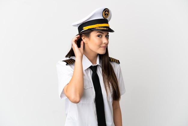 Fille brésilienne pilote d'avion sur fond blanc isolé écoutant quelque chose en mettant la main sur l'oreille