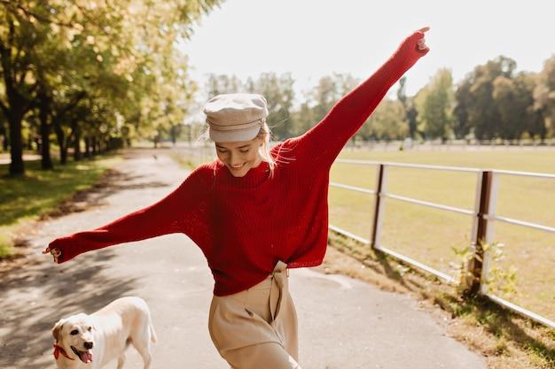 Fille brillante s'amusant avec son chien dans le parc en automne. femme blonde souriante dansant par temps ensoleillé avec son labrador.