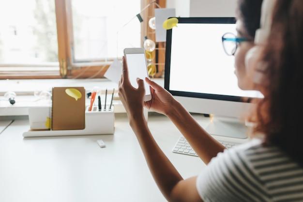 Fille bronzée en chemise d'été à rayures à l'aide de smartphone assis à la table avec un ordinateur dessus