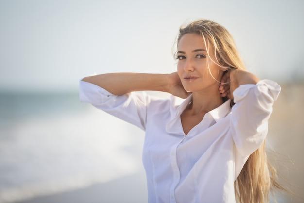 Une fille bronzée avec de longs cheveux blonds dans un maillot de bain bleuté délicat et une chemise blanche légère, traverse ses longs cheveux sur le rivage d'une mer agitée