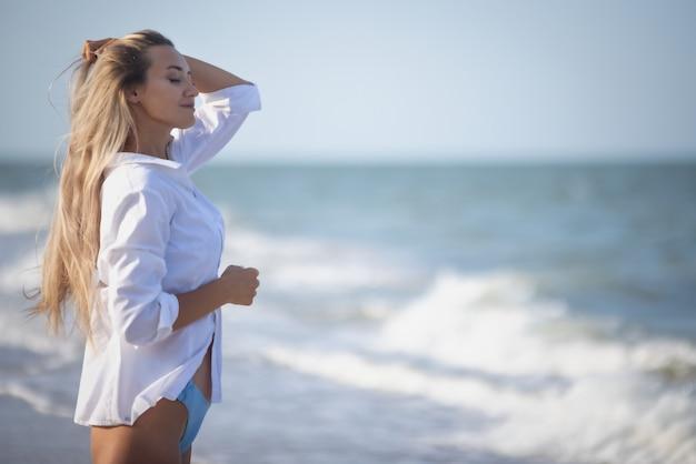 Une fille bronzée avec de longs cheveux blonds dans un maillot de bain bleuté délicat et une chemise légère blanche, traverse ses longs cheveux sur le rivage d'une mer agitée