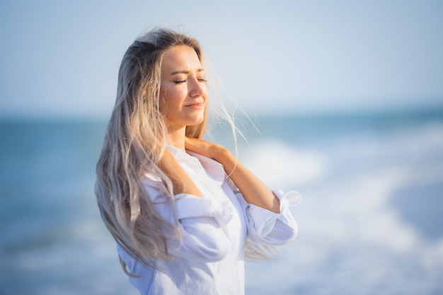 Une fille bronzée en maillot de bain bleu et chemise légère profite de l'été au bord de la mer