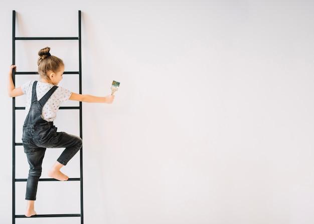 Fille avec brosse sur échelle près du mur