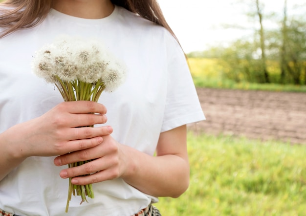 Fille brune aux cheveux longs avec bouquet de pissenlits dans le jardin d'été au coucher du soleil. place pour le texte.