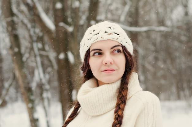 Fille brune aux cheveux longs marchant dans un parc d'hiver et jouant avec la neige, vêtu d'un pull blanc et d'un chapeau blanc fait main