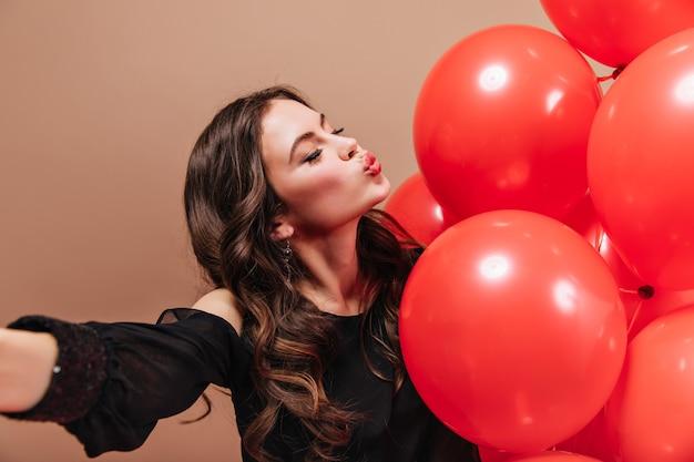 Fille brune aux cheveux ondulés prend selfie, souffle baiser et tient des ballons rouges.