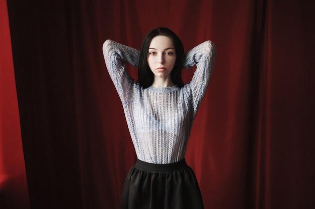 Fille brune aux longs cheveux noirs et raides avec une pose de maquillage naturelle sur le rouge. une femme en pull bleu.
