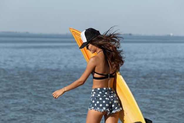 Une fille brune aux lunettes de soleil et une casquette vêtue d'un soutien-gorge noir et d'un short en jean se tient près de la mer et tient dans ses mains une planche de surf jaune par une journée ensoleillée.