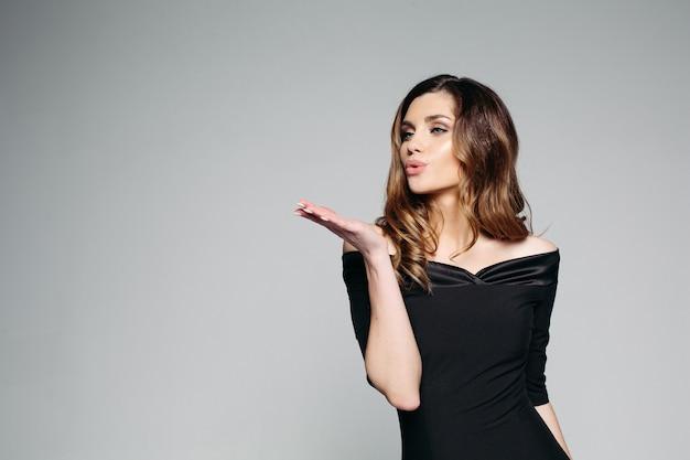 Une fille brune avec de beaux cheveux ondulés dans une élégante robe noire.