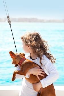 Fille brune avec chien sur la mer