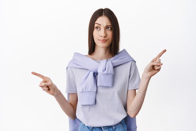 Une fille brune confuse et indécise ne peut pas faire son choix, pointant sur le côté et regardant le côté gauche, choisissant, décidant entre deux manières, debout sur un mur blanc