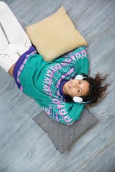 Fille brune détendue écoutant de la musique gisant sur le sol de sa maison. espace pour le texte.