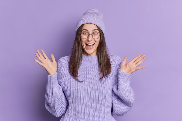 Une fille brune du millénaire positive lève les paumes et réagit à quelque chose d'impressionnant qui se tient très heureux porte un chapeau et un pull.