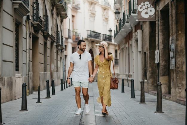 Une fille brune élégante au chapeau et son petit ami avec une barbe marchent ensemble au centre de la vieille rue européenne en espagne le soir. un couple de jeunes touristes profite de valence.