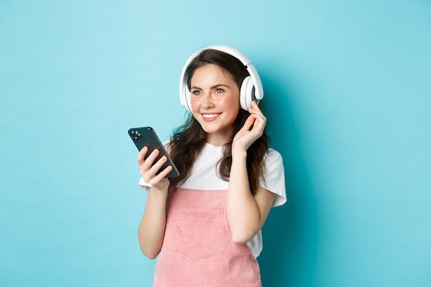 Fille brune élégante dans des écouteurs tenant un smartphone, écoutant de la musique, choisissant une piste dans une application de streaming, debout sur fond bleu.