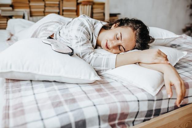 Une fille brune endormie se trouve au lit avec un bandeau