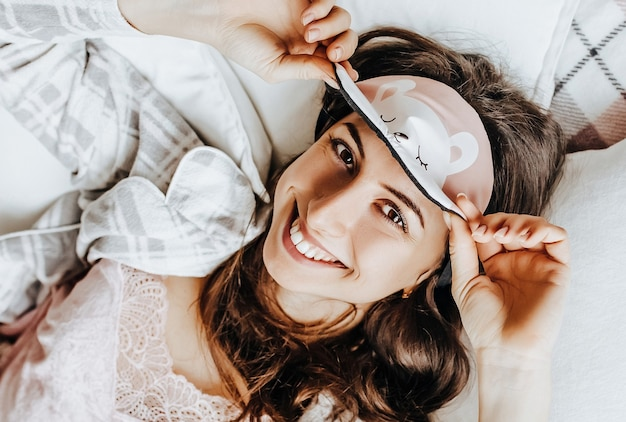 Une fille brune endormie se trouve dans son lit avec un bandeau se réveillant le matin