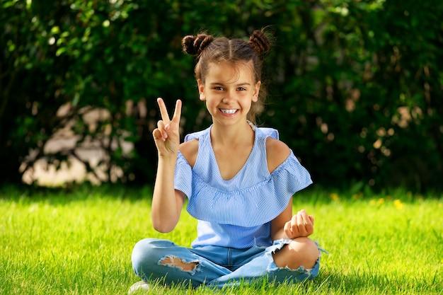 Une fille brune est assise sur l'herbe dans le parc et montre deux doigts. geste de victoire. photo de haute qualité