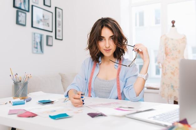Une fille brune est assise à la table dans l'atelier. elle a une chemise bleue et un désordre créatif sur la table. elle tient des lunettes et un crayon dans les mains et regarde la caméra.
