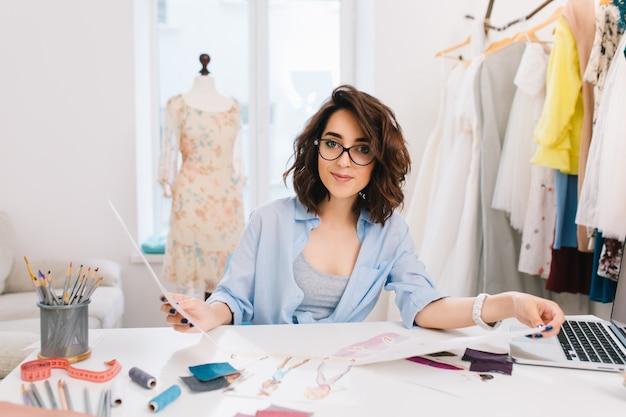 Une fille brune est assise à la table dans l'atelier. elle tient des croquis à deux mains et semble amicale avec la caméra.