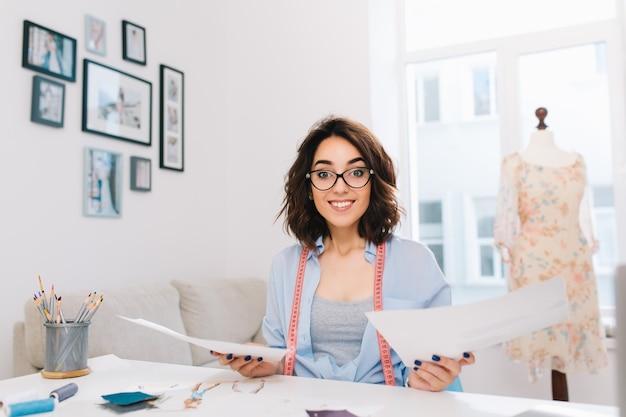 Une fille brune est assise à la table dans l'atelier. elle tient des papiers à deux mains et semble amicale avec la caméra.