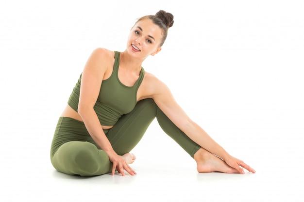 Fille brune européenne dans un costume de sport vert fait du yoga