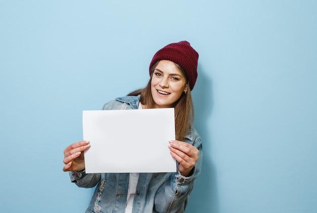 Une fille brune heureuse qui a un panneau blanc dans sa main et est heureuse sur un fond bleu