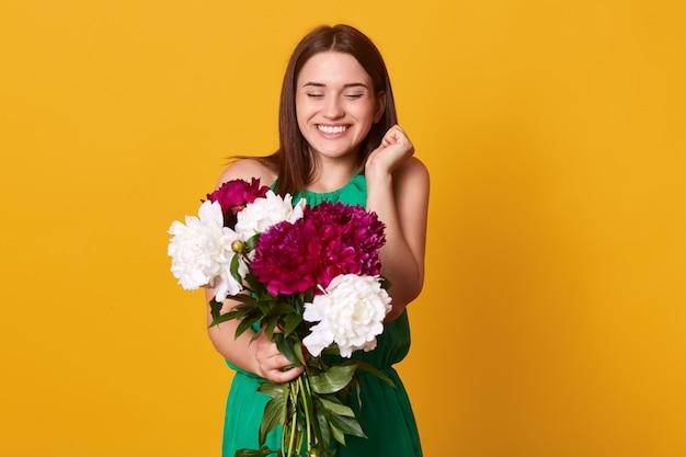 Fille brune heureuse, se tient avec le sourire et tenant le bouquet de pivoines blanches et bourgogne, exprime la joie et la joie, a un cadeau pour les vacances, a l'air excité. concept d'émotions de personnes.