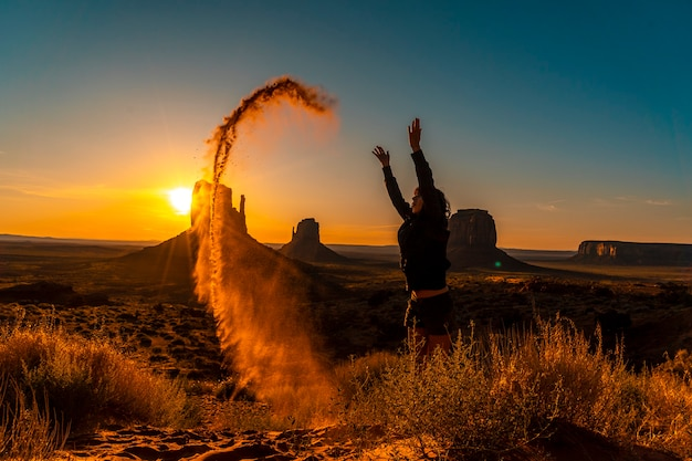 Une fille brune lifestyle à l'aube de monument valley jouant avec le sable rouge, utah