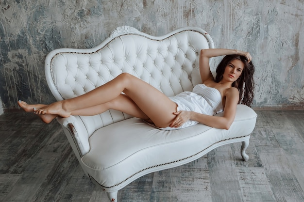 Fille brune avec de longues jambes maigres allongée sur un canapé blanc