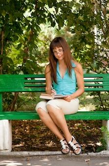 Fille brune à lunettes à faire ses devoirs dans le parc.
